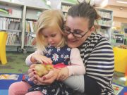Lucy Irwin from Ballan with daughter Clara, inspect the new chickens hatched at the Lerderderg Library. Photo – Jessica Howard