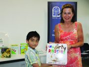 Mary Moore, committeemember of the Victorian branch of CBCA hands a book to 5-year-old Gurshaan to take home and read. Photo – Jessica Howard