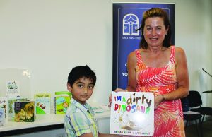 Mary Moore, committee member of the Victorian branch of CBCA hands a book to 5-year-old Gurshaan to take home and read. Photo – Jessica Howard